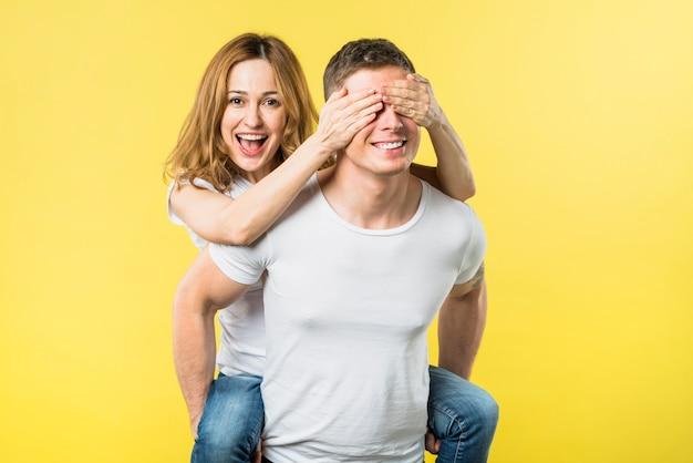 Mujer joven feliz que cubre los ojos mientras monta la espalda de su novio contra el fondo amarillo
