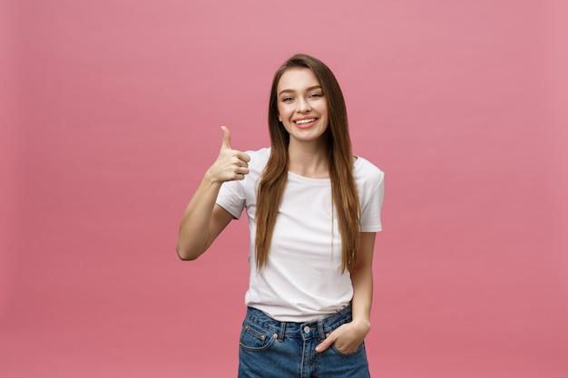Mujer joven feliz que da los pulgares para arriba en fondo rosado.