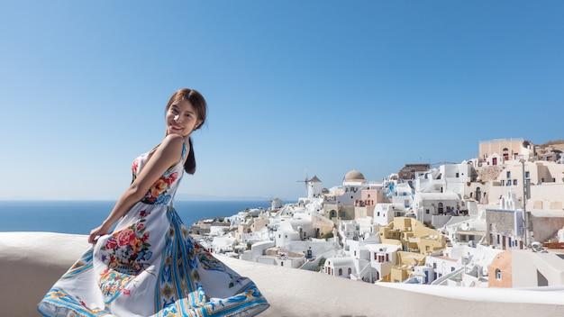 Mujer joven feliz que disfruta de la aldea de la visión oia en la isla de santorini, grecia.