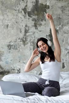 Mujer joven feliz que disfruta de música en cama