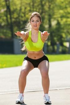 Mujer joven feliz que ejercita al aire libre