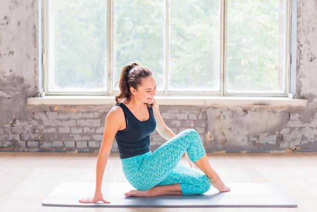 Mujer joven feliz que ejercita en la estera del ejercicio