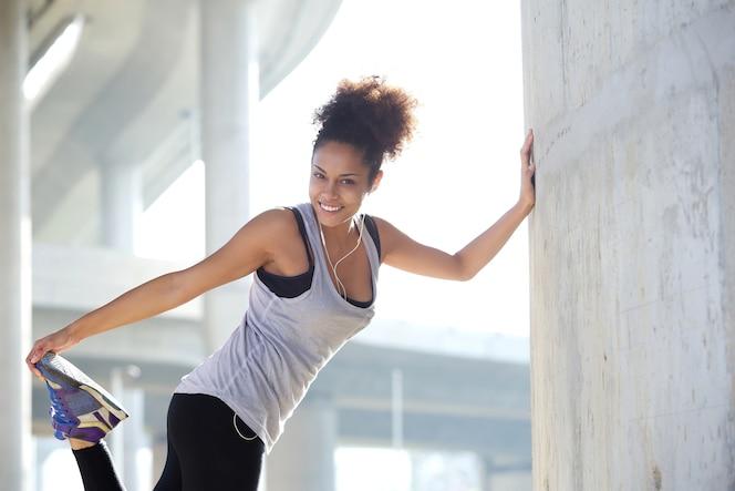 Mujer joven feliz que estira los músculos de la pierna al aire libre