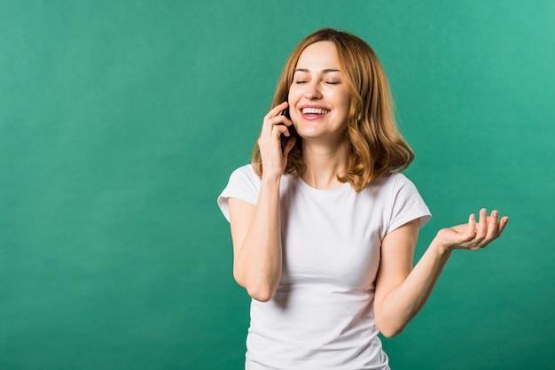 Mujer joven feliz que habla en el teléfono celular contra fondo verde
