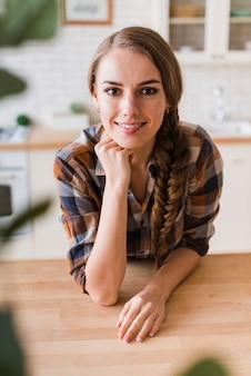 Mujer joven feliz que se inclina en la tabla en casa