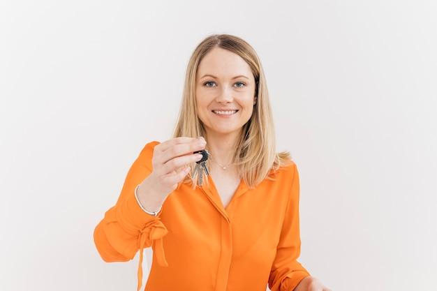 Mujer joven feliz que lleva a cabo llaves contra la pared blanca
