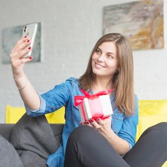 Mujer joven feliz que lleva a cabo el presente de cumpleaños que toma el selfie con el teléfono móvil