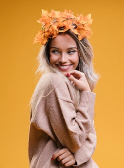 Mujer joven feliz que lleva la tiara y que presenta contra la pared amarilla
