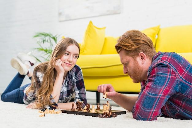 Mujer joven feliz que miente en la alfombra que mira a su novio que juega al ajedrez en la sala de estar