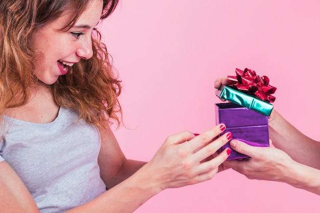 Mujer joven feliz que mira el asimiento abierto de la caja de regalo de su amigo contra fondo rosado