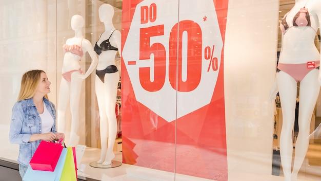 Mujer joven feliz que mira la exhibición de la ventana de una tienda de ropa