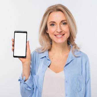 Mujer joven feliz que muestra la pantalla en blanco de la pantalla móvil contra el fondo blanco