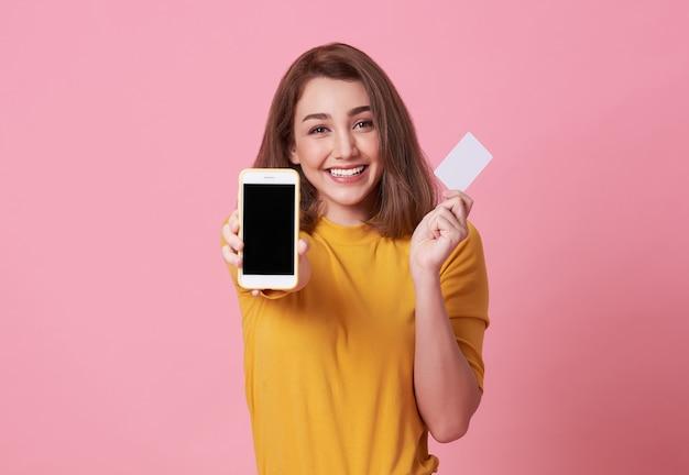 Mujer joven feliz que muestra en la pantalla en blanco teléfono móvil y tarjeta de crédito aislados en rosa.