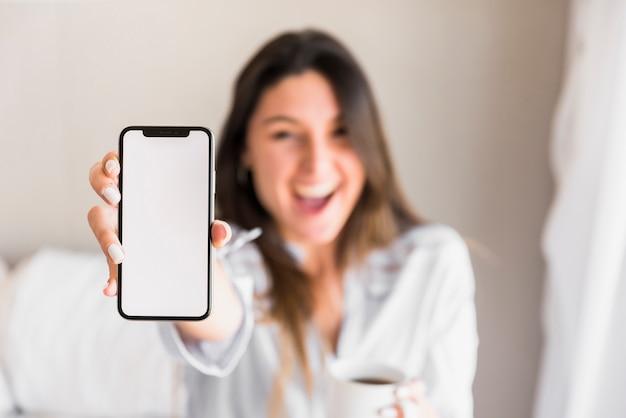 Mujer joven feliz que muestra el teléfono móvil de la pantalla blanca