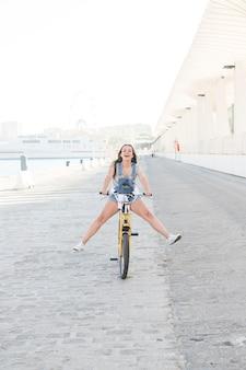 Mujer joven feliz que se divierte mientras que monta la bicicleta