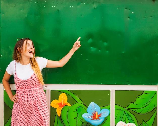 Mujer joven feliz que señala el dedo en la pared verde
