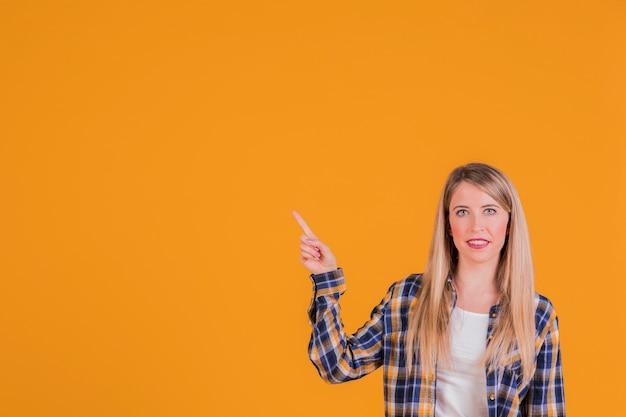Mujer joven feliz que señala su dedo hacia arriba contra un fondo naranja
