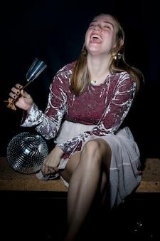 Mujer joven feliz que se sienta en banco con el vidrio del champán