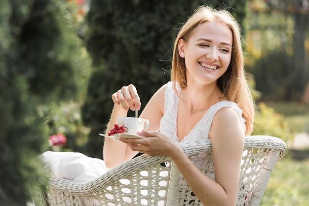 Mujer joven feliz que se sienta en la silla blanca que revuelve el café con la cuchara