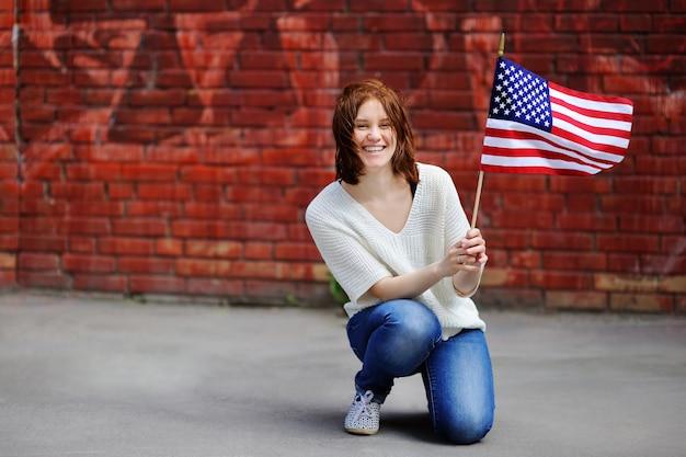 Mujer joven feliz que sostiene la bandera americana. concepto de día de la independencia.