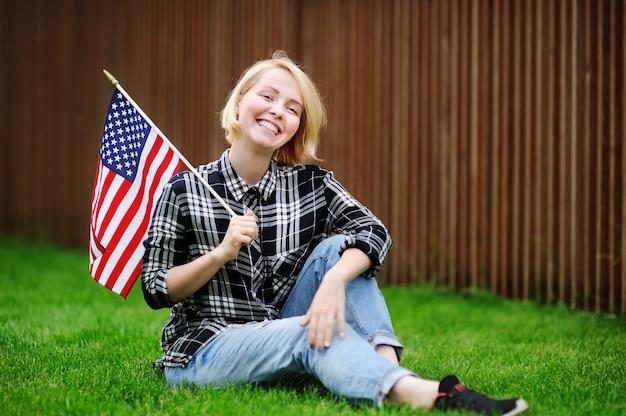 Mujer joven feliz que sostiene la bandera americana.