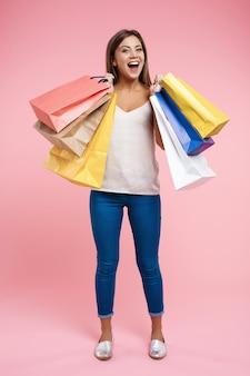 Mujer joven feliz que sostiene bolsos de compras quedándose en la pared rosada