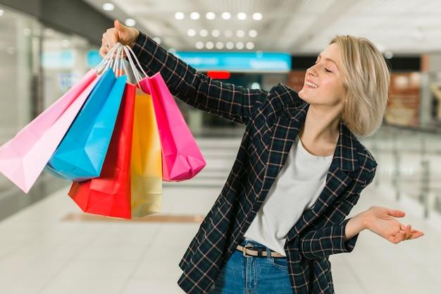 Mujer joven feliz que sostiene bolsos de compras