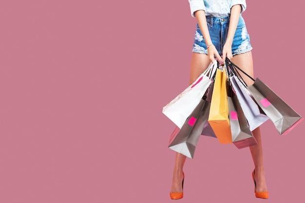 Mujer joven feliz que sostiene bolsos de compras en un fondo rosado