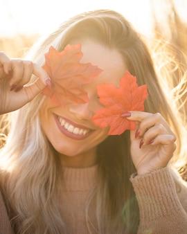 La mujer joven feliz que sostiene las hojas de arce y cubre sus ojos en el aire libre