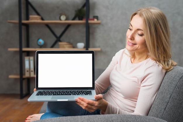 Mujer joven feliz que sostiene mirarla un ordenador portátil abierto que muestra la pantalla de visualización blanca