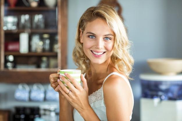 Mujer joven feliz que sostiene la taza de café en casa