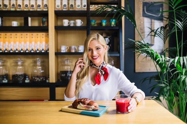 Mujer joven feliz que sostiene el teléfono móvil en la mano que se sienta en el escritorio con pan y jugo cocidos