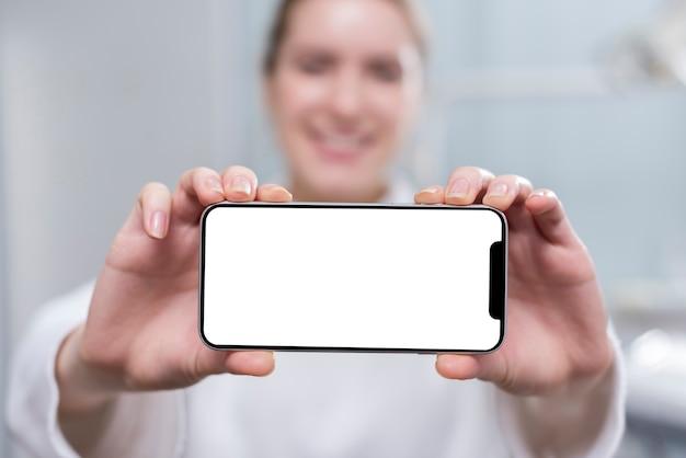 Mujer joven feliz que sostiene el teléfono móvil