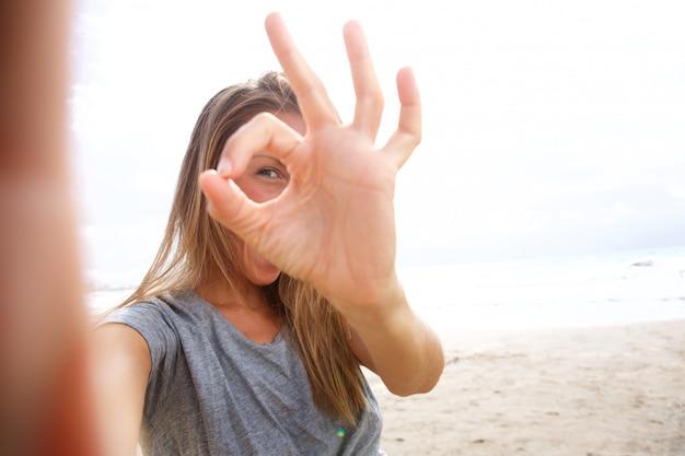 Mujer joven feliz que toma la foto del selfie con la muestra aceptable de la mano