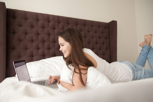 Mujer joven feliz que usa la computadora portátil en dormitorio