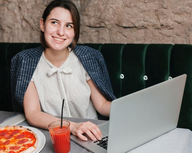 Mujer joven feliz que usa la computadora portátil