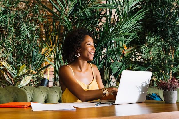Mujer joven feliz que usa el ordenador portátil con los documentos y la tableta digital en la tabla de madera