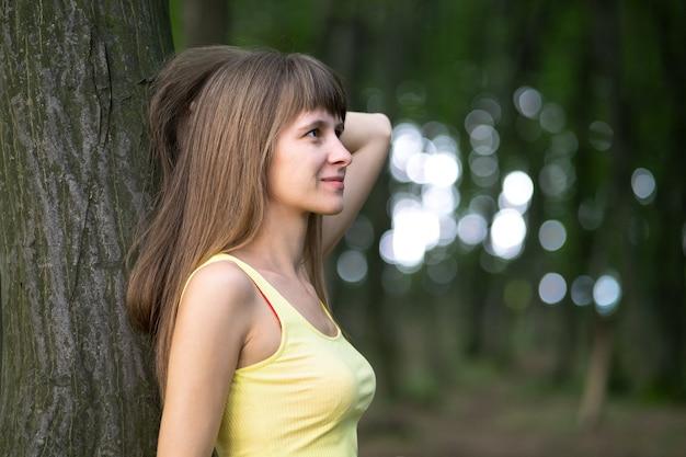 Mujer joven feliz relajante mientras se inclina a un gran tronco de árbol en el parque de verano.