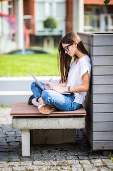 Mujer joven feliz en ropa casual y gafas usando una computadora portátil moderna y tomando notas mientras está sentado en el banco en la calle de la ciudad