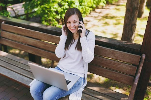 Mujer joven feliz en ropa casual ligera hablando por teléfono móvil. mujer sentada en un banco trabajando en un moderno ordenador portátil en la calle al aire libre en la naturaleza. oficina móvil. concepto de negocio autónomo.