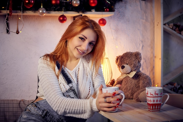 Mujer joven feliz en la sala de decoración de navidad.