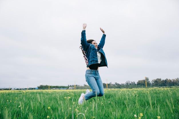Mujer joven feliz saltando en el campo