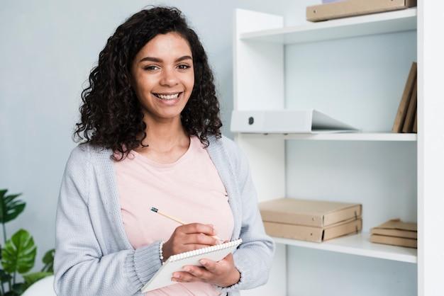 Mujer joven feliz con scratchpad en oficina