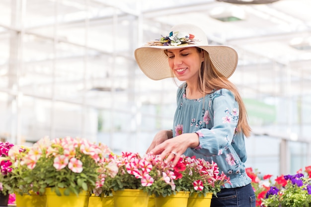 Mujer joven feliz seleccionando una planta de petunia