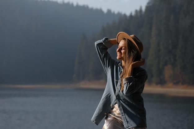 La mujer joven feliz en sombrero disfruta de la vista al lago en bosque. momentos relajantes. vista de chica elegante disfruta de la frescura al aire libre. libertad, gente, estilo de vida, viajes y vacaciones.