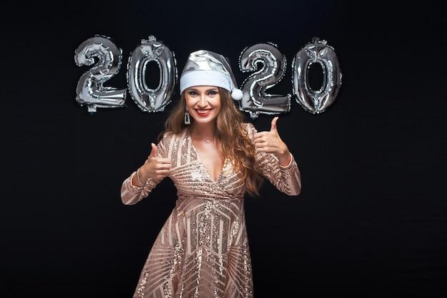 Mujer joven feliz en el sombrero de santa que muestra el pulgar para arriba gesto.
