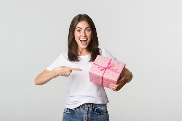 Mujer joven feliz sorprendida sonriendo y señalando con el dedo al regalo envuelto.
