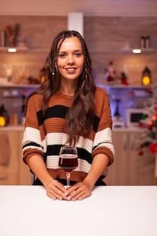 Mujer joven feliz sosteniendo una copa de vino en la cocina