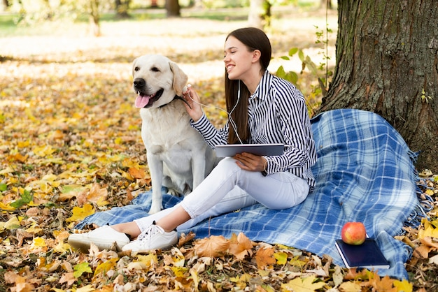 Mujer joven feliz con su perro en el parque