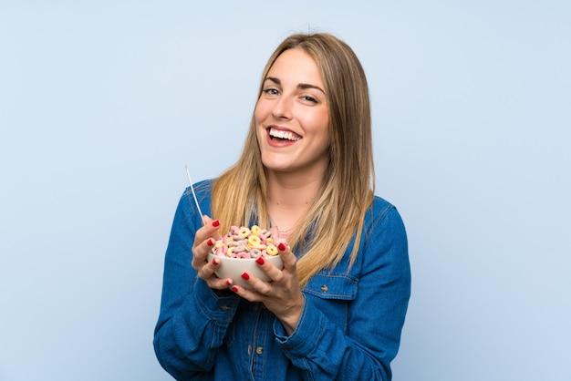 Mujer joven feliz con tazón de cereales sobre pared azul aislado